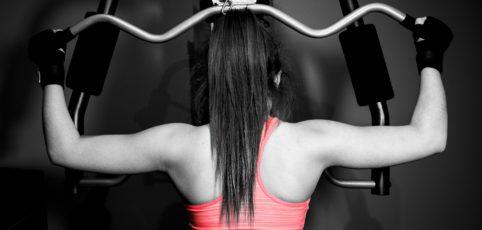 Frau von hinten mit schwarzem langem Haar beim Krafttraining
