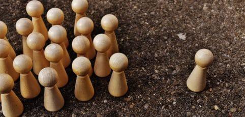 mehrere Spielfiguren links, eine alleine rechts