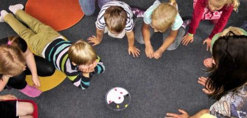 Kinder liegen im Kreis am Boden ein Spiel zusammen spielend