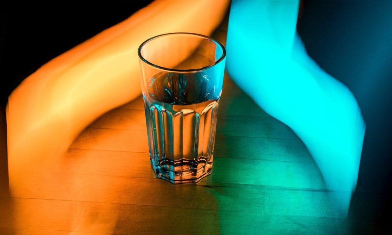 Ein Glas Wasser links von orangem, rechts von blauem Licht beleuchtet