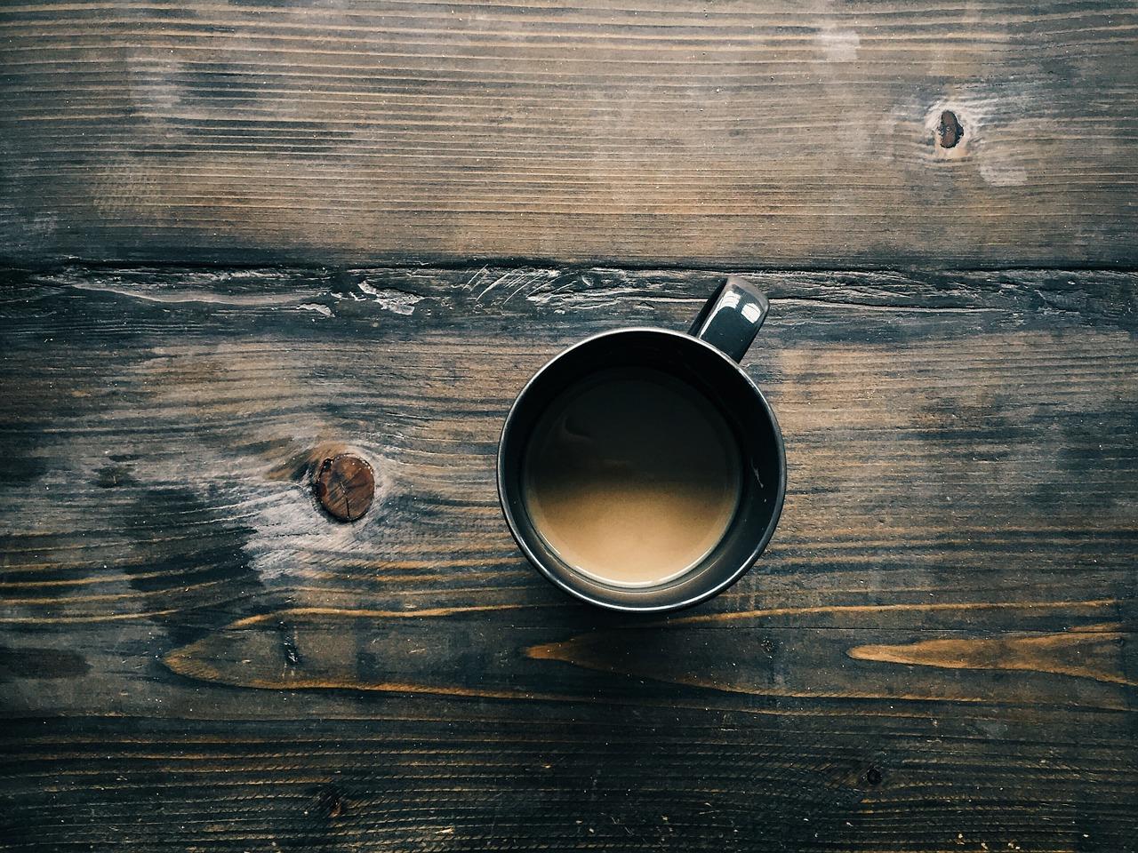Tasse mit Kaffee auf Holztischplatte