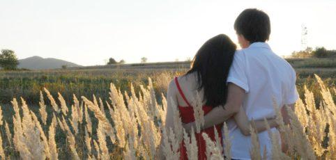 verliebtes Paar spaziert Arm in Arm in den Sonnenuntergang