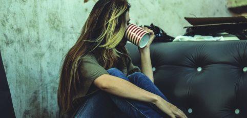 Frau sitzt am Boden und trinkt Kaffee