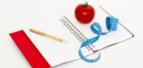 Tomate auf einem Notizbuch mit Stift und Maßband fürs Abnehmen