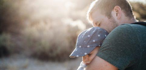 Ein stolzer Vater mit seinem kleinen Jungen im Arm