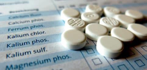 weiße Tabletten auf einem Übersichtsblatt der Schüsslersalze