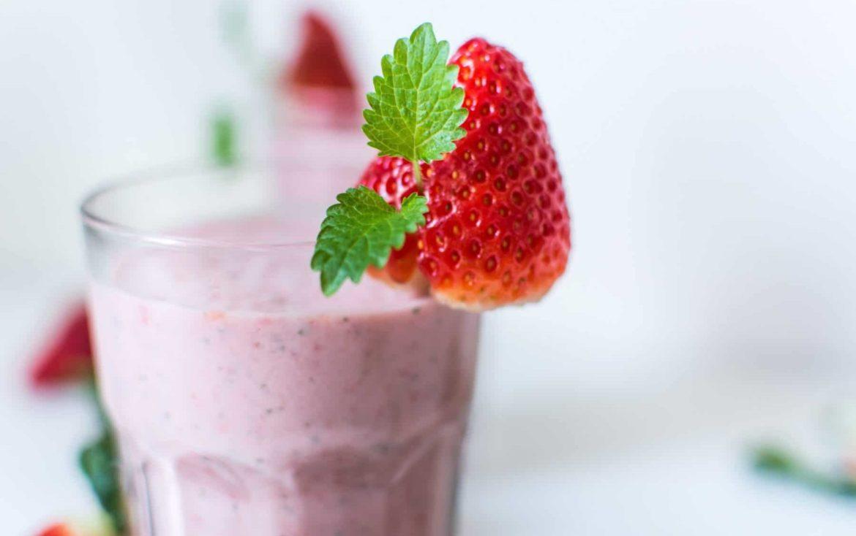 Glas mit Erdbeere Protein Shake und Erdbeere garniert