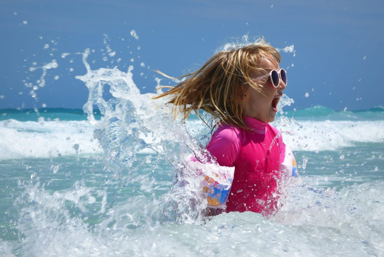 kleines Mädchen mit Schwimmflügeln im Meer am quitschen vor Spaß mit den Wellen