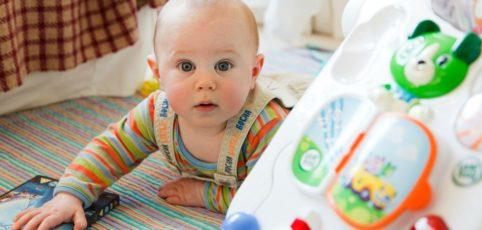 Baby krabbelt und schaut überrascht in die Kamera