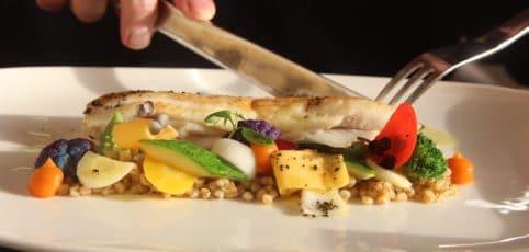 jemand ist gerade dabei ein gesundes Gericht zu essen mit Fisch und Gemüse
