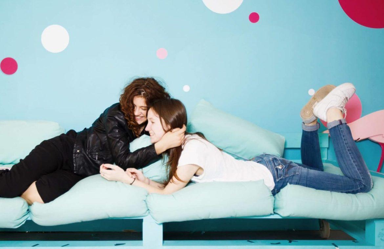 2 junge Mädels lustig am quatschen auf buntem Sofa