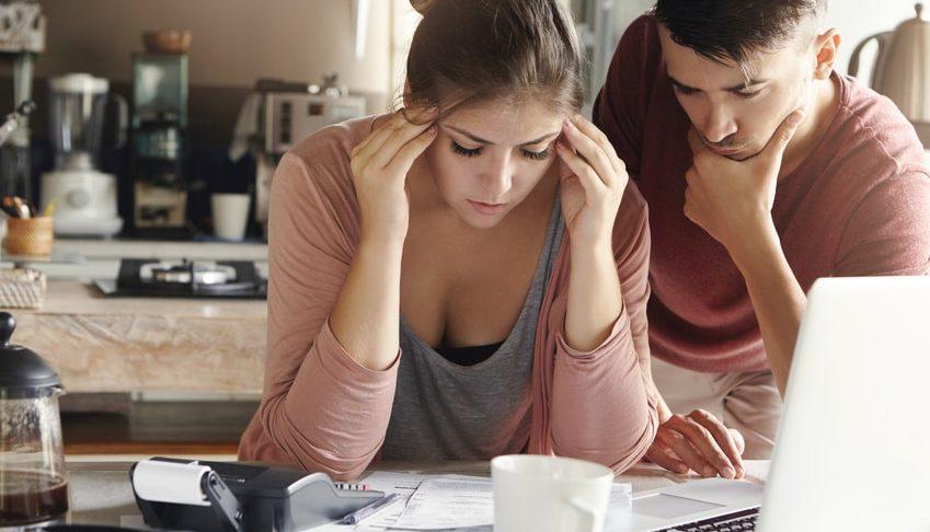ein Paar mit Geldsorgen über Rechnungen gebeugt und am verzweifeln