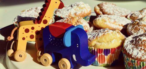 Muffins und Holzspielzeug auf einem Tisch zum Kindergeburtstag
