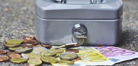 Kleine graue Geldkassette mit Geld drum herum