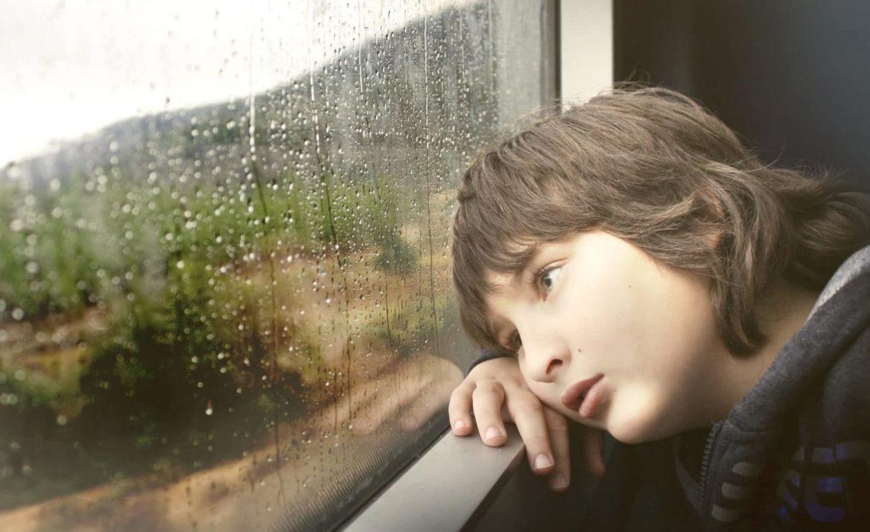 Kleiner Junge der bei Regen am Fenster sitzt, nach draussen sieht und sich langweilt