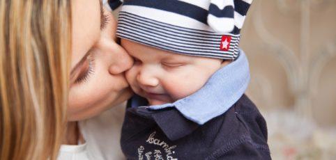 Eine Mama küsst ihr mit Baby auf die Wange