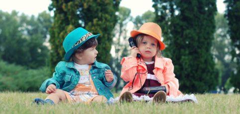 zwei kleine Mädels auf der Wiese mit Hüten am spielen