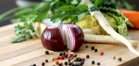 Rote Zwiebel auf Holzbrett sowie Pfeffer und frische Kräuter