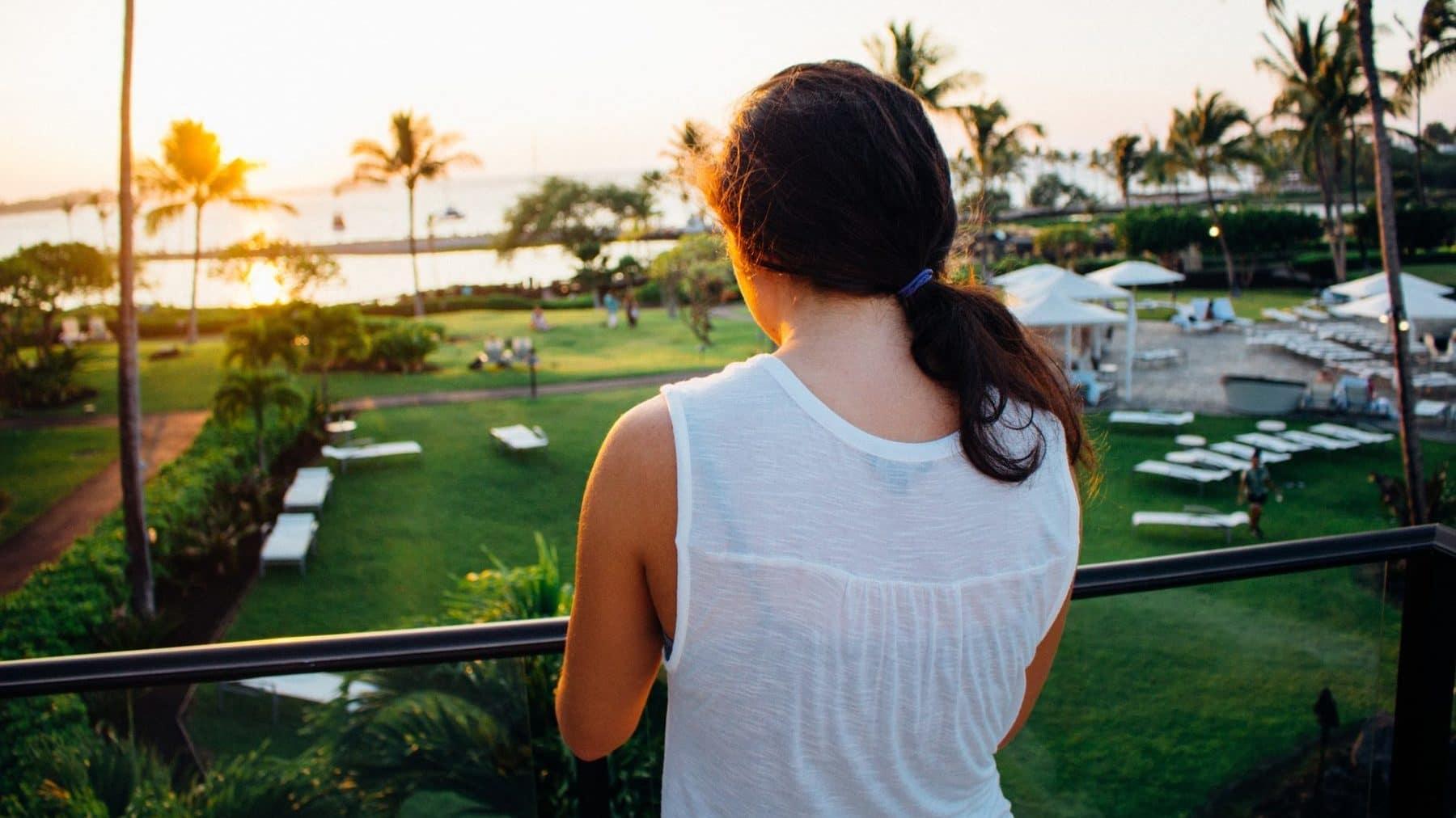 Frau steht auf dem Balkon ihres Hotelzimmers und schaut hinaus