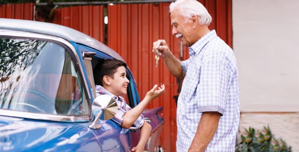 Opa überreicht seinem im Auto sitzenden Enkel die Autoschlüssel
