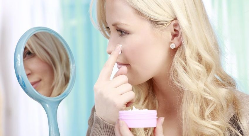 Junge blonde Frau cremt sich ihr Gesicht ein und hält dabei einen Kosmetikspiegel in der Hand