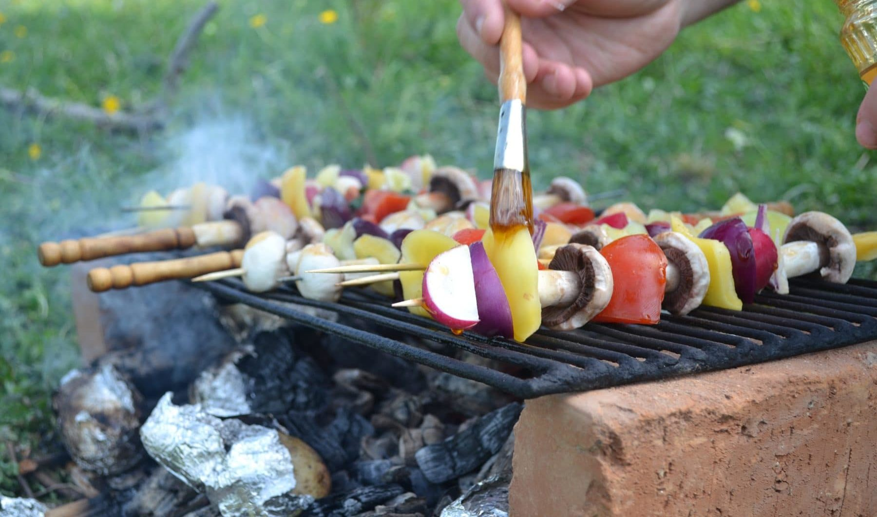 Glühender Grill mit Spießen drauf und jemand pinselt das Gemüse mit Öl ein