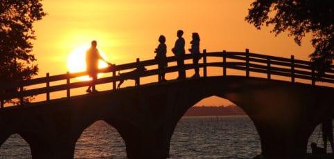 Spaziergänger auf einer Brücke die in den Sonnenuntergang sehen
