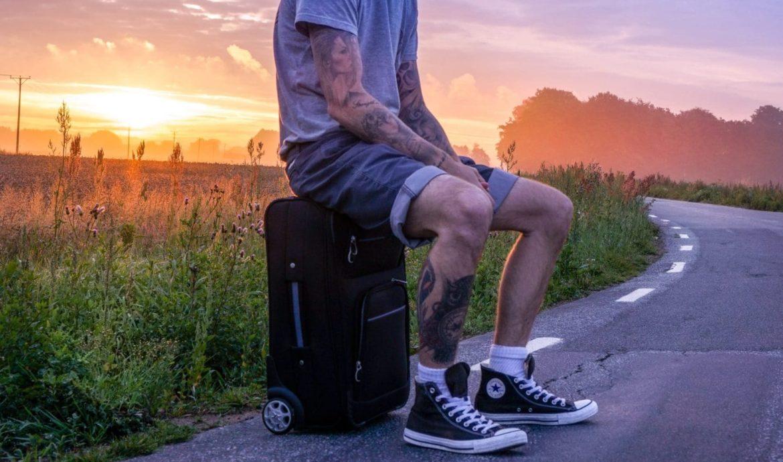 Mann sitzt auf seinem Koffer im nirgendwo, wartet abgeholt zu werden