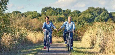älteres Ehepaar am Fahrrad fahren und Händchen haltend