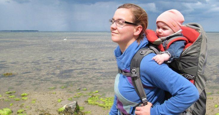 Baby in der Trage auf dem Rücken der Mutter unterwegs am Meer