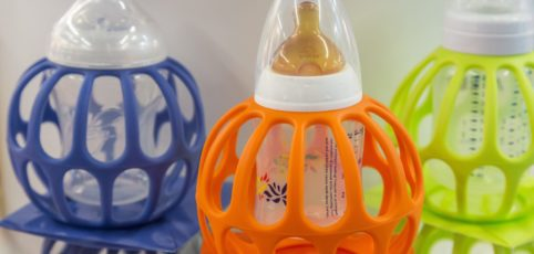 Drei Babyflaschen mit bunten Halterungen