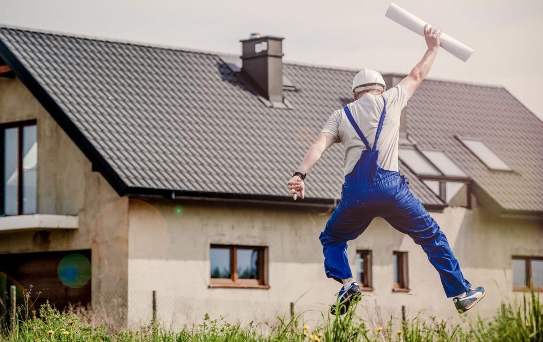 Mann in blauer Latzhose springt und freut sich über sein neues Haus