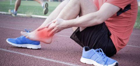 Mann am Boden mit schmerzendem Fußgelenk