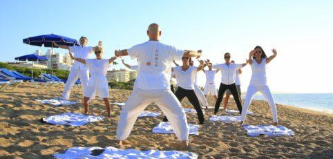 Eine Gruppe Menschen mit unterschiedlichem Alter machen Übungen am Strand