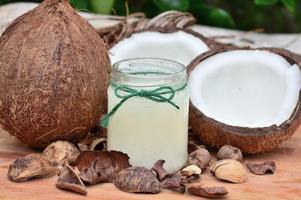 Kokosnussöl im Glas mit Kokosnüssen