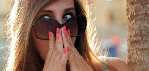 Frau mit langen offenen Haaren, Sonnenbrille und rot lackierten Nägeln