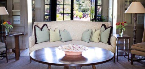 Ein gemütliches Sofa mit Kissen in einem schönen Wohnzimmer mit Blick zur Terrasse und Garten