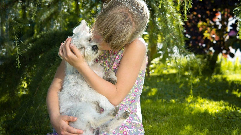 Mädchen schmust mit Hund der das offensichtlich sehr genießt