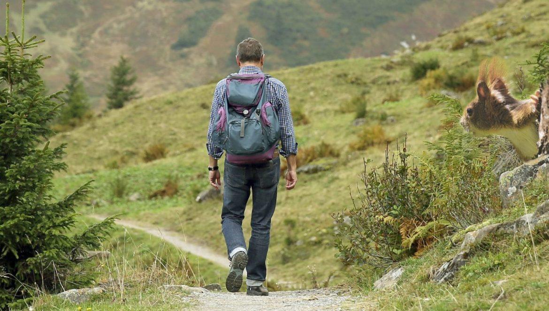 Ein Mann wandert in den Bergen mit Rucksack und Wanderstiefeln