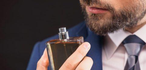 Junger Mann riecht an seinem Herrenduft