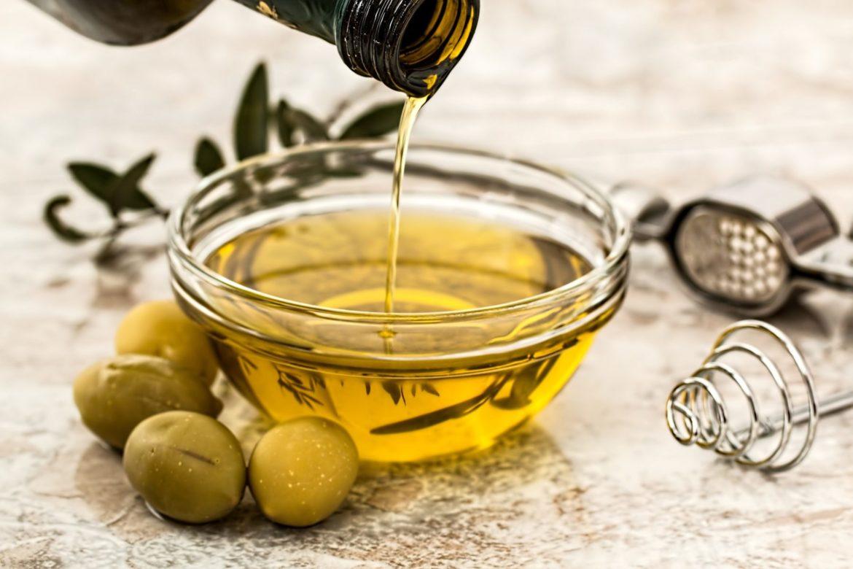 Schale Olivenöl und grüne Oliven daneben