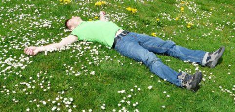 Ein Mann liegt auf einer grünen Wiese und entspannt