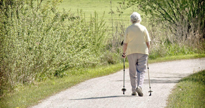 Alte Frau ist mit Nordc Walking unterwegs