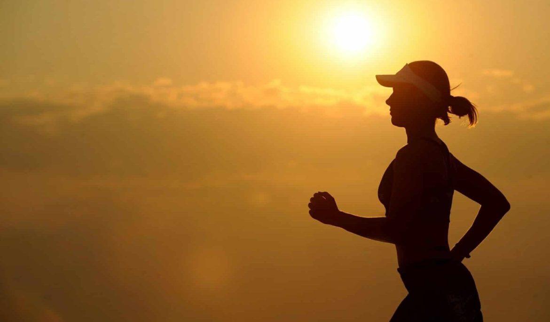Frau beim Joggen vor aufgehender Sonne