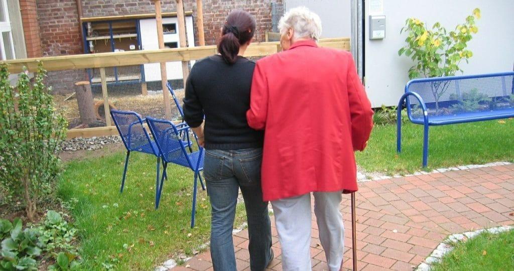 Oma mit Stock bei jüngerer Frau am Arm gestützt