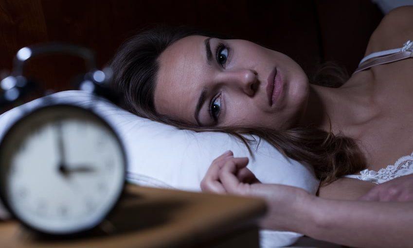 Frau liegt schlaflos im Bett morgens um 3 Uhr mit Blick auf den Wecker