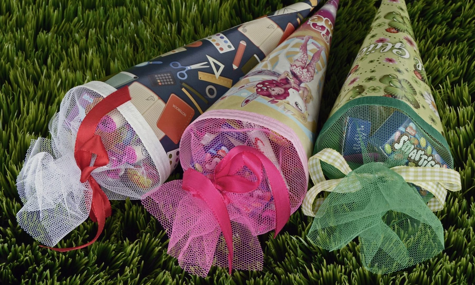 Drei Schultüten in verschiedenen Farben und bunten Schleifen