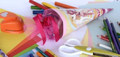 Schultüten und Utensilien für den Schulanfang auf einem Kindertisch