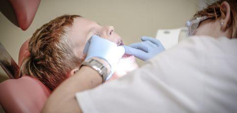 Ein Kind auf dem Behandlungsstuhl. Zahnärztin beugt sich über das Kind und untersicht die Zähne.