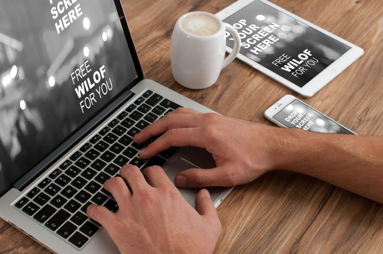 Mann vor dem Laptop mit Tablett und Smartphone neben sich